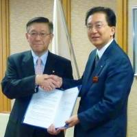 Working together: Akita Gov. Norihisa Satake (left) appears with Iwate Gov. Takuya Tasso at the Iwate Prefectural Government headquarters in Morioka on Tuesday after they signed an agreement on tsunami debris. | KYODO