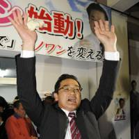 Atsushi Sakima celebrates Sunday evening at his campaign headquarters after it was confirmed that he would beat former Ginowan Mayor Yoichi Iha in hotly contested mayoral election. | KYODO PHOTO