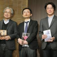 Wordsmiths: Authors (from left) Rin Hamuro, Shinya Tanaka and To Enjo hold copies of their works during a ceremony in Tokyo on Jan. 17. Enjo and Tanaka were awarded the Akutagawa Prize and Hamuro won the Naoki Prize. | KYODO