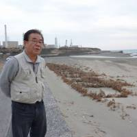 Exposed: Minoru Ito, 70, walks on the beach near the Hamaoka nuclear power plant in Omaezaki, Shizuoka Prefecture, on Feb. 5. | KYODO