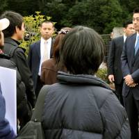 On the back foot: Environment Minister Goshi Hosono (right) faces local residents Thursday who are opposed to the incineration of tsunami debris from Iwate Prefecture in Shimada, Shizuoka Prefecture. | KYODO