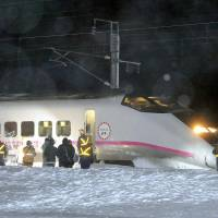 Off the rails: The front car of a bullet train on the Akita Shinkansen Line lies in heavy snow following its derailment Saturday in the city of Daisen, Akita Prefecture. | KYODO