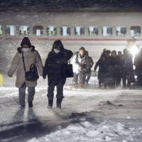 Biting the bullet: Passengers make their way from a bullet train that derailed Saturday amid heavy snow on the Akita Shinkansen Line in the city of Daisen, Akita Prefecture. | KYODO