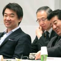 Real politics: Osaka Mayor Toru Hashimoto (left), coleader of Nippon Ishin no Kai (Japan Restoration Party), and Osaka Gov. Ichiro Matsui (right), Nippon Ishin secretary general, attend a party meeting Saturday in Osaka. | KYODO
