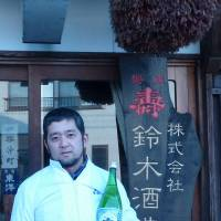 Living tradition: Daisuke Suzuki, a sake brewer, holds a bottle of his product on Feb. 15 in front of a brewery he bought in Nagai, Yamagata Prefecture. | KYODO