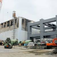 A makeshift cap is being built for the remnants of the reactor 4 containment building before Tokyo Electric Power Co. begins removing fuel rods from its spent-fuel pool in November. | POOL