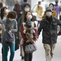 Haz-masks: Fukuoka residents venture outdoors wearing masks Saturday to protect themselves against a cloud of yellow sand that is drifting across from China.   KYODO