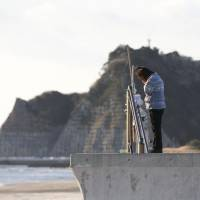A woman on the coast of Tairausuiso in Iwaki, Fukushima Prefecture, prays Monday for family members killed in the earthquake and tsunami on March 11, 2011. | KYODO