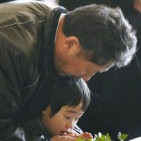 A man and child pray at a memorial ceremony in Kamaishi, Iwate Prefecture, the same day. | KYODO