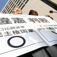 Constitutional confrontation: Plaintiffs and lawyers hold up a sign declaring 'unconstitutional judgment' in front of the Tokyo High Court on March 6 after it ruled that December's Lower House election was unconstitutional. | KYODO