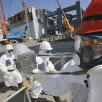 Hazard pay: A worker at the Fukushima No. 1 nuclear complex gets a radiation reading of 114 microsieverts per hour on March 6 near reactor 4, which stands surrounded by cranes next to the concrete foundations for a storage facility for melted fuel rods. | POOL