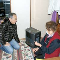 Face to face: Shuichi Maki (left), director of the nonprofit organization Yorozu Sodankai, speaks with a resident of a replacement housing complex in Kobe on Feb. 5. | KYODO