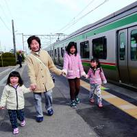 A woman and her grandchildren get off at Hamayoshida Station in Watari, Miyagi Prefecture, after a damaged part of the Joban Line resumed service Saturday for the first time since the March 2011 quake and tsunami.