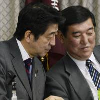 Easy does it: Prime Minister Shinzo Abe (left) confers with Liberal Democratic Party Secretary General Shigeru Ishiba during a meeting Saturday at the ruling party's Tokyo headquarters. | KYODO