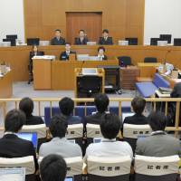 Common language: A courtroom at the Naha District Court in Okinawa is seen on Feb. 26. When needed, interpreters occupy the empty seats at right, below the judges. | KYODO