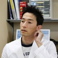 All ears: Haruka Nakanishi, a doctor at the University of Miyazaki's Faculty of Medicine, speaks during an interview there in November. | KYODO