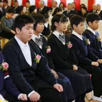 Baby steps: Namie Elementary School students from Fukushima Prefecture attend a graduation ceremony Friday in Nihonmatsu, where the school evacuated to after the 3/11 disasters. | KYODO