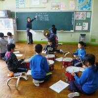 Upbeat: Pupils attending Kisai Elementary School in Kazo, Saitama Prefecture, practice a medley of songs from Kisai and two Fukushima elementary schools in February. | KYODO