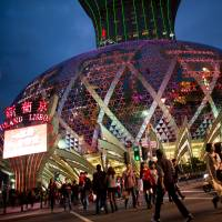 Place your bets: Pedestrians cross an intersection in front of the Casino Grand Lisboa, operated by SJM Holdings Ltd., in Macau in February. Diet members are considering submitting a bill to legalize casinos like this. | BLOOMBERG