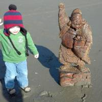 Lucky find: A child on a beach in Washington state poses Monday next to a statue of Ebisu that apparently was swept into the sea by the 2011 tsunami. | ALISON NELSON/KYODO