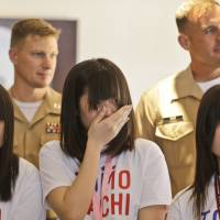 Deepest thanks: U.S. Marine Master Sgt. Howard Tait (right) and Capt. Ben Middendorf stand behind an emotional Mami Onotera on  Tuesday as she and other students from Kesennuma, Miyagi Prefecture, visit San Diego to thank the marines who provided disaster relief in 2011. | AP