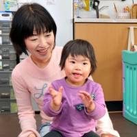 Mariko Otake, 2, who was born with Down syndrome, plays with her mom, Noriko, in their home in Shinjuku Ward on March 7. | YOSHIAKI MIURA