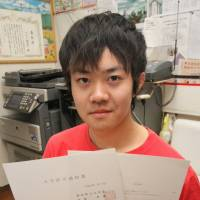 College bound: Rafael Yukio Kusuki shows his acceptance letter from Aichi Prefectural University at a shelter for the homeless in Ichinomiya, Aichi Prefecture, this month. | CHUNICHI SHIMBUN