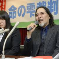Small comfort: Tsutomu Shimabuku, whose son, Hideyoshi, died as a result of a combat drill in 2006 when he was a Ground Self-Defense Force private at Camp Makomanai in Sapporo, faces reporters Friday in the city along with his wife, Ritsuko, after a court ordered the government to pay ¥65 million in damages over the death. | KYODO