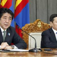 In sync: Prime Minister Shinzo Abe (left) and Mongolian Prime Minister Norov Altankhuyag hold a joint news conference in Ulan Bator following their meeting Saturday. | KYODO