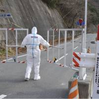 Off limits: A police officer in protective suit stands by a warning sign at a checkpoint on Route 114 on the edge of the 20-km hot zone around the Fukushima No. 1 nuclear plant in Namie, Fukushima Prefecture, in December. | KYODO