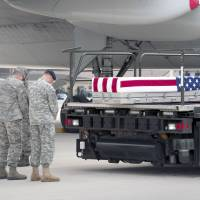 The human cost: U.S. Army and Air Force officers pray as the remains of army Sgt. Michael Cable arrive at Dover Air Force Base, Delaware, on Thursday. Cable was killed in Afghanistan during Operation Enduring Freedom.  | AP
