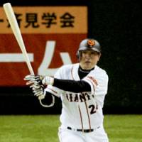 Yomiuri Giants' Yoshinobu Takahashi hits a go-ahead RBI infield single in the fifth inning against the Hanshin Tigers at Tokyo Dome on Thursday. The game ended in a 2-2 tie. | KYODO PHOTO