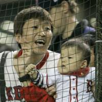 A Red Sox fan and a baby enjoy Major League Baseball's Opening Day action on Tuesday at Tokyo Dome.   AP PHOTO