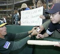 Athletics hitting coach Ty Van Burkleo hands a fan a baseball with his autograph on it before Wednesday's game at Tokyo Dome. Van Burkleo played for the Seibu Lions from 1987-90. | AP PHOTO