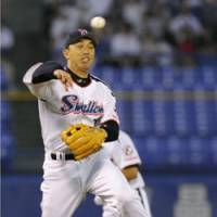 On the hop: Tokyo Yakult Swallows third baseman Shinya Miyamoto picks up a grounder by Yuki Yoshimura of the Yokohama BayStars and throws to first for an out during the fourth inning on Tuesday at Jingu Stadium. The Swallows won 4-1. | KYODO PHOTO