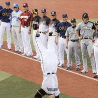 Time to clown around: Nippon Ham Fighters outfielder Hichori Morimoto walks onto the field doing a headstand during the opening ceremony for Game 2 of the NPB All-Star Series. | KYODO PHOTO
