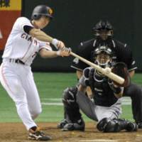 Solid contact: Giants slugger Michihiro Ogasawara smacks the 300th homer of his career in the seventh inning against Hanshin at Tokyo Dome on Friday. Yomiuri beat the Central League-leading Tigers 6-4. | KYODO PHOTO