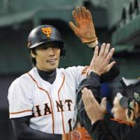 Job well done: Takahiro Suzuki takes the plaudits from the Yomiuri bench after scoring the Giants' first run of their 6-4 win over the Seibu Lions in Game 3 of the Japan Series on Tuesday. | KYODO PHOTO