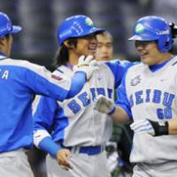 Welcome home: Seibu's Yasuyuki Kataoka and Hiroshi Hirao congratulate Takeya Nakamura after the third baseman hit a three-run homer in the second inning of the Lions' 16-2 win over Tianjin on Saturday. | KYODO PHOTO