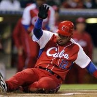 Still in the hunt: Cuba's Michel Enriquez slides home safely with a run against Mexico on Monday night in a World Baseball Classic second-round game in San Diego. | AP PHOTO