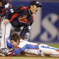South Korea's Lee Yong Kyu steals second base ahead of Yasuyuki Kataoka's tag during Japan's 4-1 defeat at the World Baseball Classic in San Diego on Tuesday. Japan faces Cuba in an elimination game Wednesday. | AP PHOTO