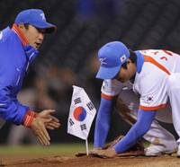 Staking a claim: South Korean starting pitcher Bong Jung Keun and teammate Lee Jin Young plant their country's flag on the mound in PETCO Park after defeating Japan in the World Baseball Classic on Tuesday in San Diego. | AP PHOTO