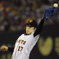 At a stretch: Giants starting pitcher Shun Tono attempts to make a catch during Yomiuri's 4-1 win over the Hanshin Tigers on Saturday. | KYODO PHOTO