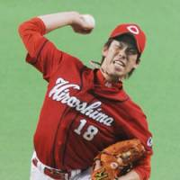 Solid performance: Hiroshima Carp starter Kenta Maeda delivers a pitch against the Hokkaido Nippon Ham Fighters on Tuesday at Sapporo Dome. Maeda pitched eight scoreless innings in the Carp's 2-1 win. | KYODO PHOTO