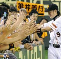 Fan favorite: Yoshiyuki Kamei greets Giants fans and exchanges high-fives with them after Yomiuri's dramatic triumph over the Swallows on Saturday at Tokyo Dome. | KYODO PHOTO
