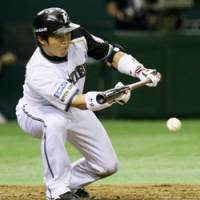 Focused on the ball: Nippon Ham Fighters catcher Shinya Tsuruoka makes a squeeze bunt for the leadoff run in the fifth inning against the Orix Buffaloes on Tuesday at Tokyo Dome. | KYODO PHOTO