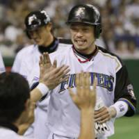 High five!: Fighters first baseman Eiichi Koyano celebrates with teammates after scoring the go-ahead run on Yoshio Ito's single in a four-run fifth inning against the Buffaloes at Tokyo Dome on Thursday. Hokkaido Nippon Ham won 8-4. | KYODO PHOTO