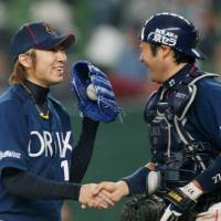 Never too late: Orix reliever Chihiro Kaneko shakes hands with catcher Takeshi Hidaka after claiming his first save in two years. | KYODO PHOTO