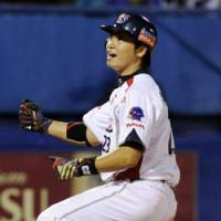 Playoff bound: Yakult outfielder Norichika Aoki reacts as he scores on Ryohei Kawamoto's single in the sixth inning against Hanshin at Jingu Stadium on Friday. The Swallows won 3-1 and captured a Climax Series berth.   KYODO PHOTO