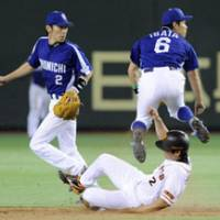 Going for two: Chunichi shortstop Hirokazu Ibata completes a double play as Yomiuri runner Michihiro Ogasawara is forced out while second baseman Masahiro Araki looks on at Tokyo Dome on Wednesday. The Dragons beat the Giants 7-2. | KYODO PHOTO